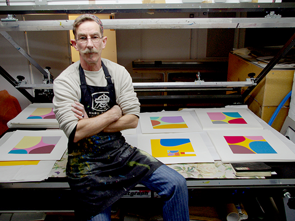 Click the image for a view of: Artist at the silkscreen press